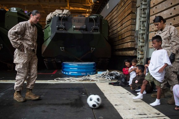 U.S. Marines with the 15th Marine Expeditionary Unit play soccer with an Indonesia child while he waits to be transported to an Indonesian coast guard vessel from the USS Rushmore (LSD 47), June 11, 2015. The child, along with 64 other distressed mariners were rescued from a sinking craft in the waters between the Indonesian islands of Kalimantan and Sulawesi. (U.S. Marine Corps photo by Sgt. Emmanuel Ramos/Released)