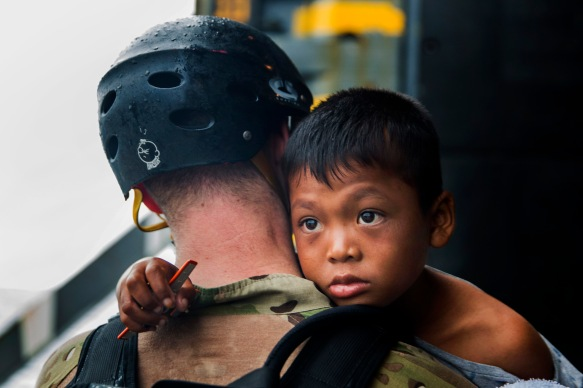 A U.S. Sailor with the Essex Amphibious Ready Group loads an Indonesia boy onto a watercraft to be transported to an Indonesian coast guard vessel from the USS Rushmore (LSD 47) in the Pacific Ocean, June 11, 2015. Rushmore rendered assistance to the distressed mariners in the waters between the Indonesian islands of Kalimantan and Sulawesi. Once on board, the mariners were provided food and medical attention by Marines and Sailors of the 15th Marine Expeditionary Unit and Essex Amphibious Ready Group. (U.S. Marine Corps photo by Sgt. Emmanuel Ramos/Released)