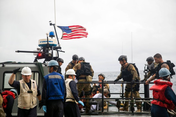U.S. Marines and Sailors with the 15th Marine Expeditionary Unit and the Essex Amphibious Ready Group assist rescued mariners onto a watercraft to be transported to an Indonesian coast guard vessel from USS Rushmore (LSD 47) in the Pacific Ocean, June 11, 2015. Rushmore rendered assistance to the distressed mariners in the waters between the Indonesian islands of Kalimantan and Sulawesi while transiting the area during a deployment with the Essex ARG and 15th MEU. Once on board, distressed mariners were provided food and medical attention by Marines and Sailors of the 15th MEU and Essex ARG. (U.S. Marine Corps photo by Sgt. Emmanuel Ramos/Released)
